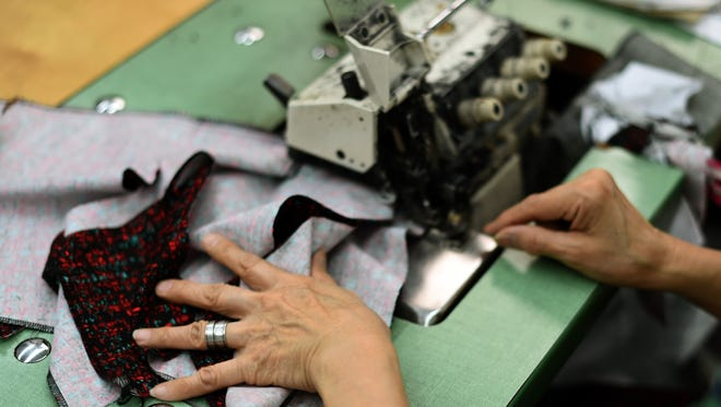 A woman sews at the High Production factory in New York's garment district on April 22, 2014.