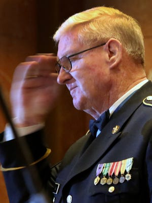 Vietnam veteran and Congressional Medal of Honor recipient Sgt. 1st Class Sammy L. Davis salutes after speaking, and upon receiving the 2018 Sachem Award, from Gov. Eric Holcomb, during a ceremony at the Indiana War Memorial, Monday, March 12, 2018.