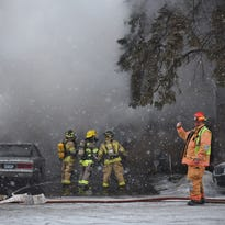 Firefighters battle smoke in the upper level of a home in Avon Thursday afternoon after responding to a call of a house fire.
