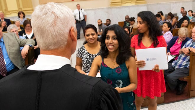 Vinusha Udayalal, 22, center, shakes Common Pleas Judge Clyde W. Vedder's hand on Thursday as she receives her citizenship certificate in the York County Administrative Center.  Her mother, Gowrieswary, 50, left, and sister, Vidusha, 28, right, also became naturalized citizens. Another sister, Laksha, 16, (not pictured), receives citizenship through her mother. The family emigrated from Sri Lanka. Forty-seven people from more than 20 countries became U.S. citizens at the naturalization ceremony.