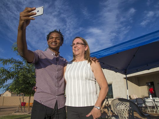 In this Thursday, Nov. 24, 2016 photo, Jamal Hinton and Wanda Dench take a selfie together after meeting at Wanda's home for Thanksgiving dinner, in Mesa, Ariz.  Dench, who accidentally texted Hinton, a stranger, an invitation to Thanksgiving dinner made good on her offer, greeting the teen visitor with a hug and an oven full of food after their story swept through social media.   (Tom Tingle/The Arizona Republic via AP)
