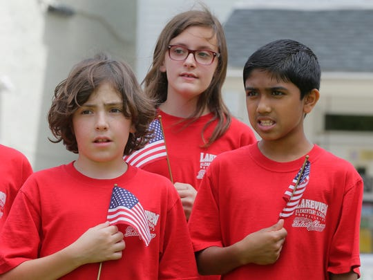 "(L-R) Alexander McMahon, 10, Ashlyn Albro, 10, and Rohith Venkateswaran, 10, members of the Lakeview Select Chorus at Lakeview School in Denville, sing ""God Bless America"" during the Morris County's Memorial Day ceremony for veterans on the lawn in front of the Morris County Courthouse in Morristown, NJ Wednesday May 24, 2017."
