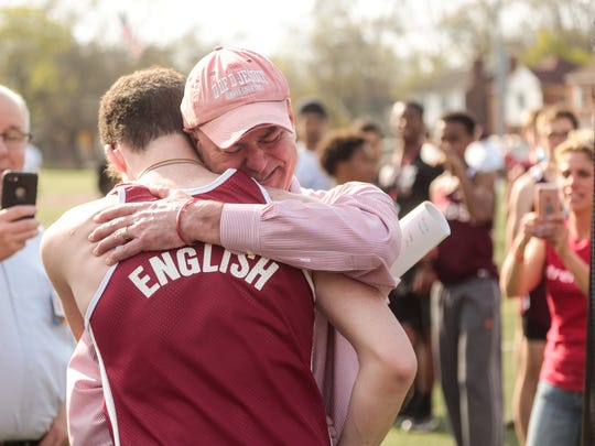 University of Detroit Jesuit High School and Academy runner Sean English is hugged by his father Sean English  after crossing the finish line in his first and last high school race on Wednesday, May 2, 2018 at the school in Detroit. English, who wore his father's jersey from when he ran for the school from 1979-81, lost his leg while stopping to help six car accident victims.