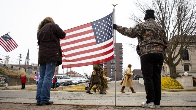 Toni Mishler, left, and Michelle Pawlak honor veterans on their day off from work at the Veterans Day parade Monday, Nov. 12, 2018 on Capitol Avenue in Springfield, Ill. The parade is canceled this year because of the COVID-19 pandemic.