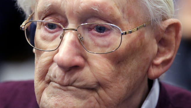 94-year-old former SS sergeant Oskar Groening listens to the verdict of his trial at a court in Lueneburg, Germany. Groening, who served at the Auschwitz death camp was convicted on 300,000 counts of accessory to murder and given a four-year sentence.