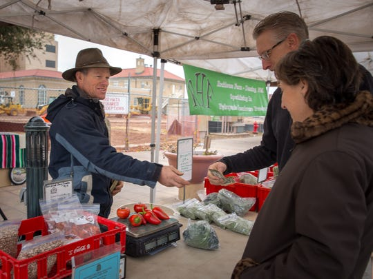 Wayne and Teresa Savage pick up their week's worth of fresh produce from Jason Nicoll of Rockhouse Farm at the Farmer's Market on Saturday morning.