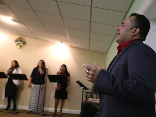 Ronal Vasquez sings along with parishioners before taking the stage to speak at the Casa de Adoracion Emanuel in Quincy, where he has been a pastor for the last four years. Vasquez has lived in the United States since 1996 on Temporary Protected Status from El Salvador, a qualification that may be ending under the current presidential administration next year.