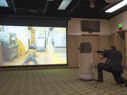 Larimer County Sheriff's Office Deputy Mark Hecker takes a tactical position during a simulation at the Larimer County Sheriff's Office on Thursday, Oct. 26, 2017. The training tool is loaded with different scenarios that require different types of force from trainees.
