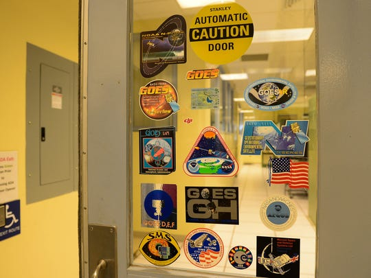 Stickers from the different GOES mission decorate the door window into where the data is received and kept from the satellites that are currently in space on Thursday, May 24, 2018 in Wallops, Va.