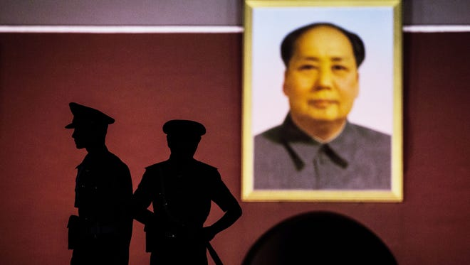 Chinese paramilitary security force officers stand under a portrait of the late Mao Zedong outside the Forbidden City at Tiananmen Square on June 2.