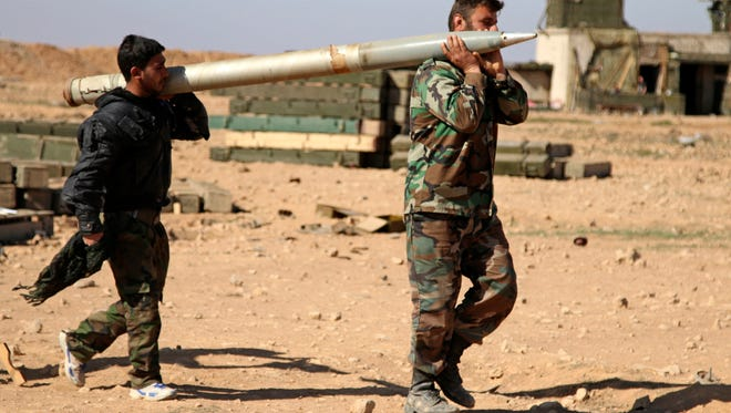 Soldiers from the Syrian army carry a rocket to fire at Islamic State group positions in the province of Raqqa, Syria.