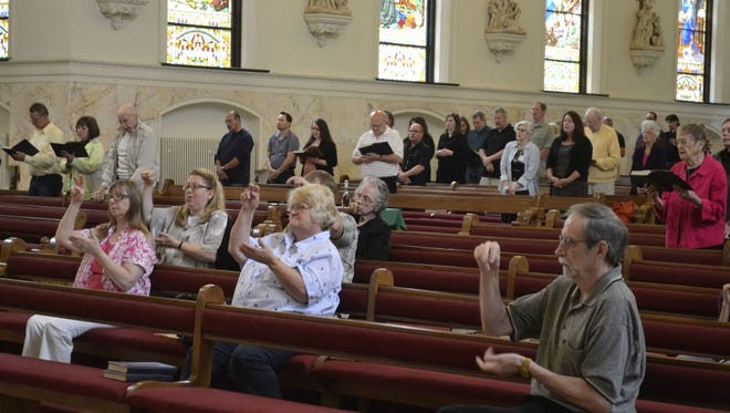 Seated in the first few rows of pews, members of the deaf community at St. John the Evangelist Parish in Green Bay sign the response as general intercessions are read during Mass on Sunday morning, June 5, 2016, at the downtown church.