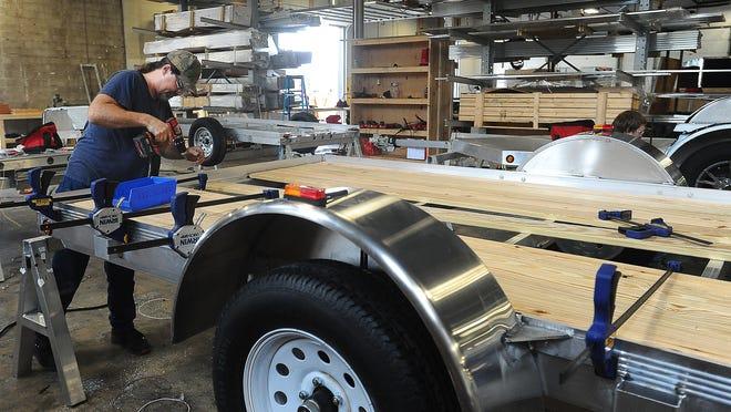 Un employé d'Alcom travaille sur une remorque à plateau dans l'usine ouverte de la société à Sioux Falls, dans le Dakota du Sud.  La société étend ses activités internationales avec une nouvelle usine à DeLand.  Une entreprise leader dans le domaine de la marine et des véhicules récréatifs envisage également de s'étendre dans le comté de Volusia.