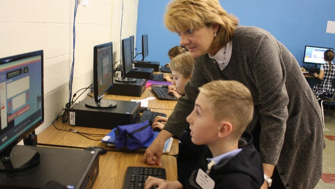 St. Thomas School Principal Deborah Flamm talks with fourth-grade student Caleb Eaglin of Cold Spring about his keyboard skills in a computer lab.