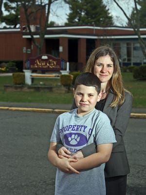 Aimee Pollak of New City with her son Ryan, a fifth-grader at New City Elementary School, outside the school Friday. Pollak has two children in the Clarkstown schools. She and her husband refused to have them take this state's standardized tests.