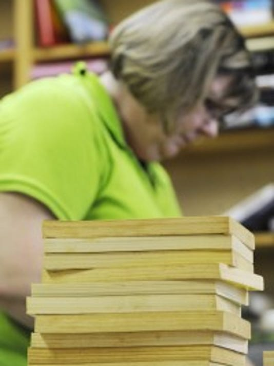 Suzanne Hatch, owner of Bay Window Books in Dallastown book store, sorts books in July before the store's closing. (YORK DAILY RECORD/SUNDAY NEWS -- JASON PLOTKIN)