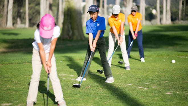 Youth golfers on the driving ranger practice their swings.