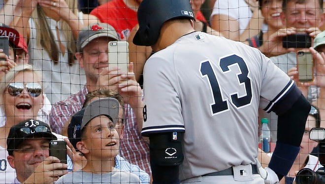 New York Yankees' Alex Rodriguez (13) talks to Jacob Doherty, 10, of Wilmington, Mass., in the on-deck circle during the first inning of a baseball game against the Boston Red Sox  in Boston, Thursday, Aug. 11, 2016.