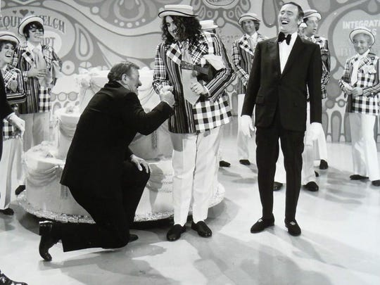 "John Wayne bends a knee to Tiny Tim during the filming of the 100th episode of ""Laugh-In"" in 1972."