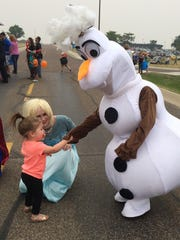 Sweet Peas Princess Rentals and More's Olaf and Elsa greet children during a family day picnic at Malmstrom Air Force Base.