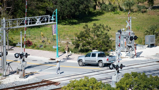 Pedestrians and vehicles move across the train tracks used by Brightline trains at East Ocean Avenue and Northeast Fourth Street on Thursday, Jan. 18, 2018, in Boynton Beach.