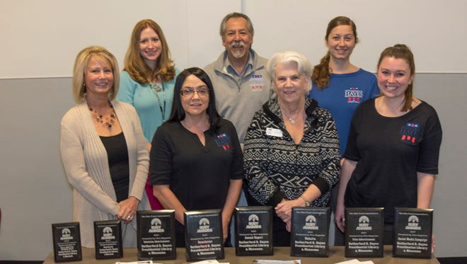 Hayes Presidential Library and Museums staff posing with awards are, from left in the front row, Kathy Boukissen, Mary Lou Halbeisen, Becky Hill, and Elizabeth Davenport, and in back, from left, Kristina Smith, Gil Gonzalez, and Meghan Wonderly.