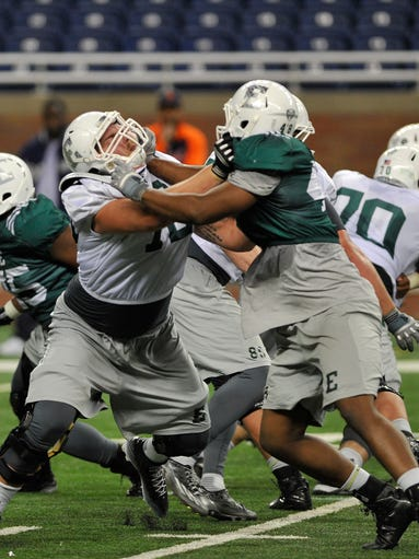 EMU offensive lineman Andrew Wylie (left) tries to