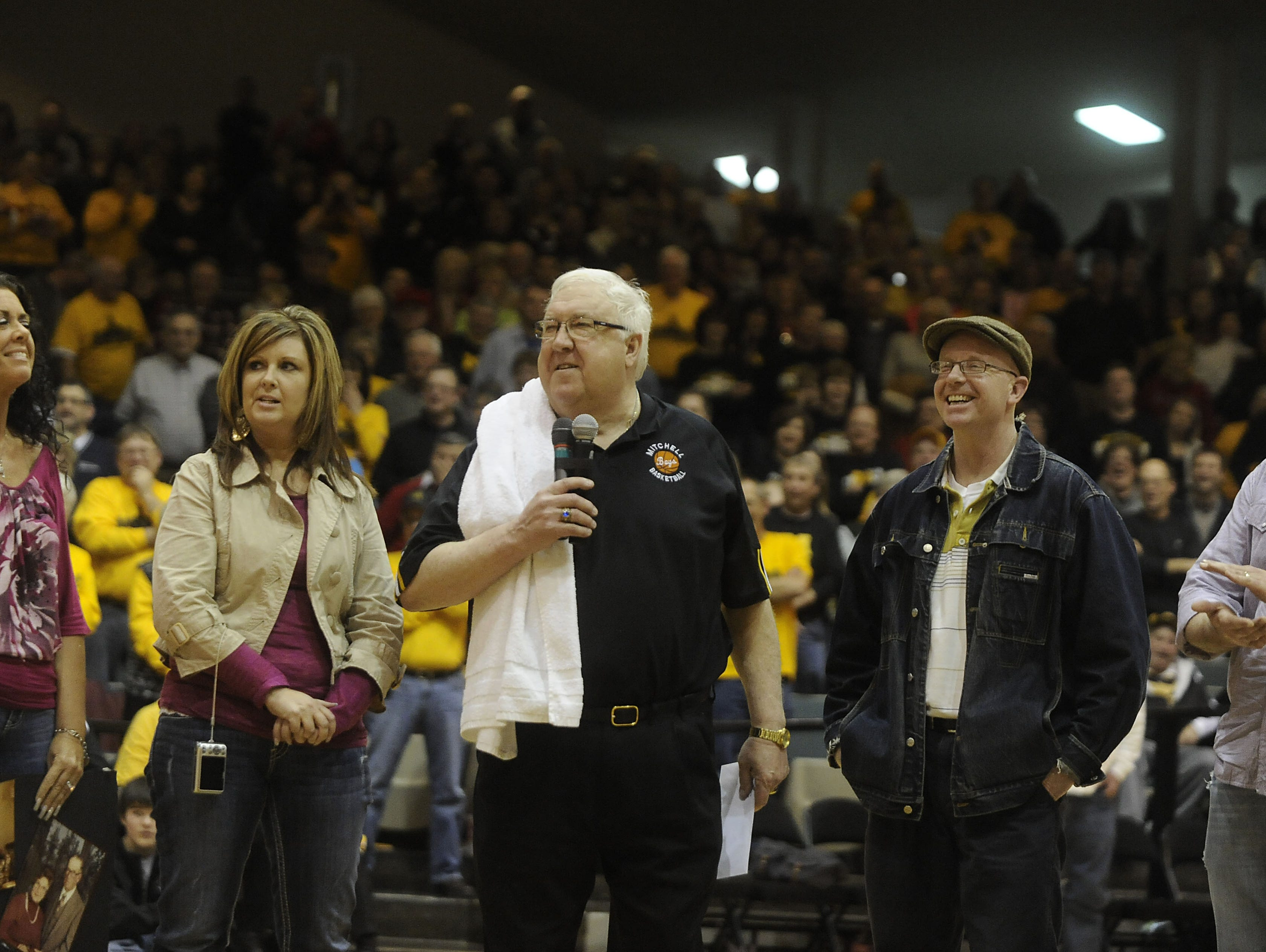 Mitchell High School boys basketball head coach Gary Munsen talks to former players, fans and spectators while his family members stand beside him after he was honored at the Corn Palace on Tuesday, Feb.14, 2012, in Mitchell, S.D. Munsen died Jan. 12, 2016.