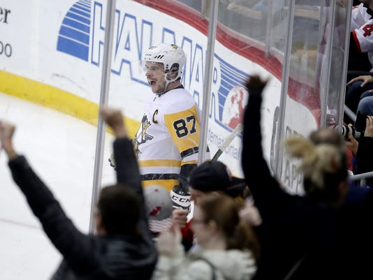 Pittsburgh Penguins center Sidney Crosby celebrates after scoring the game-winning goal during overtime in an NHL hockey game against the New Jersey Devils, Thursday, March 29, 2018, in Newark, N.J. The Penguins won 4-3. (AP Photo/Julio Cortez)