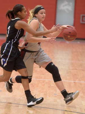 Indiana University East's Libby Springmier moves the ball against Ohio Christian University's Breyonia Hearn Saturday, Dec. 3, 2016 during a basketball game at IUE in Richmond.