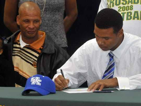 2-3-11, 1C  Catholic High School's Demarius Rancifer, right, commits to play football for the University of Kentucky on National Signing Day, while his dad Keith Rancifer, center, and niece Trinity left, look on.