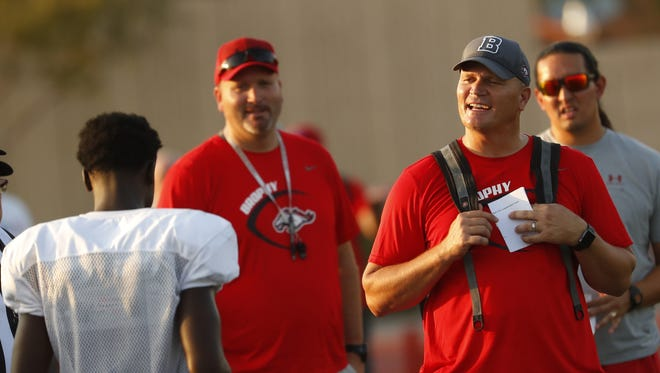 Brophy Prep's head coach Jon Kitna talks with his team during an exhibition at Brophy College Prep in Phoenix, Ariz. on Aug. 9, 2018.