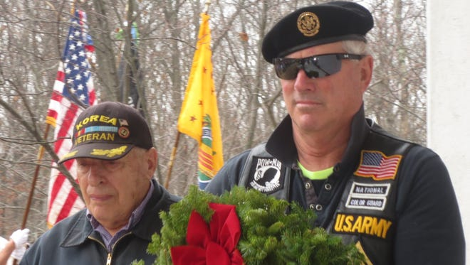 Pat Dante (left), U.S. Army Korean War veteran from Bridgewater, and Gary Stansbury, U.S. Army, from Howell, present a memorial wreath at the opening ceremony of Wreaths Across America.