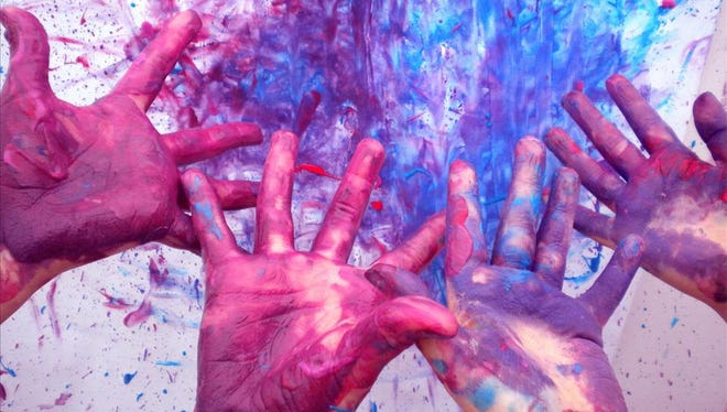 """Children show off their colorful hands from """"Paint Me a Song,"""" one of the classes in """"Art on the Wild Side."""""""