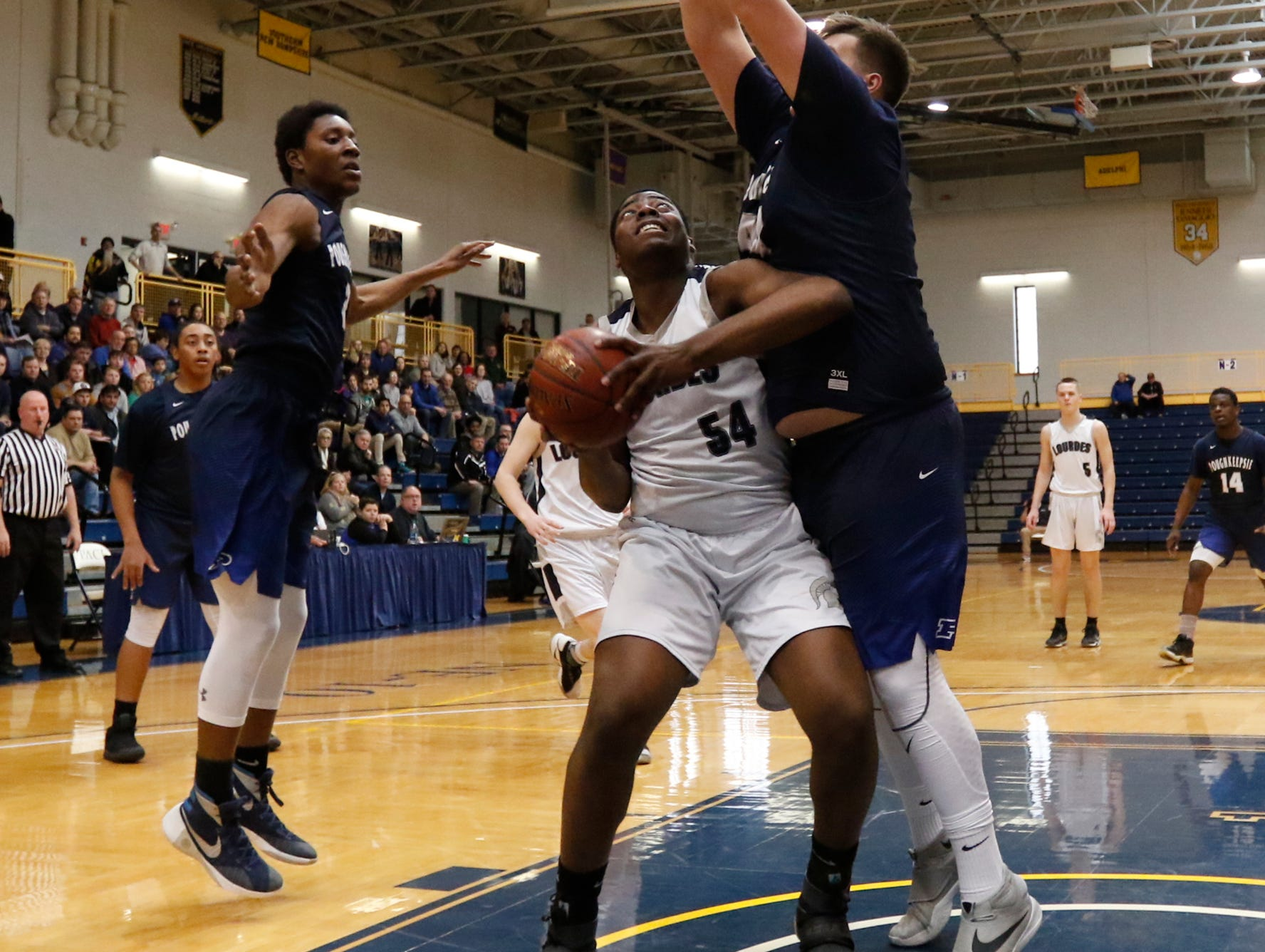 Our Lady of Lourdes High School's James Anozie looks for space as Poughkeepsie's Cory Simmons defends during the Class A regional finals at Pace University in Pleasantville on March 11.