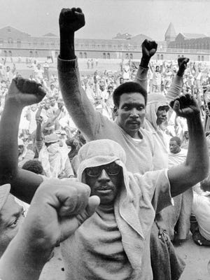 Inmates of Attica state prison raise their fists to show solidarity in their demands during a negotiation session Sept. 10, 1971.