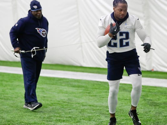 Tennessee Titans running back Derrick Henry (22) runs with a ball held on a cord by running backs coach Sylvester Croom, left, during an NFL football practice Tuesday, Jan. 2, 2018, in Nashville, Tenn. The Titans are scheduled to play the Kansas City Chiefs Saturday in an AFC wild-card playoff game. (AP Photo/Mark Humphrey)