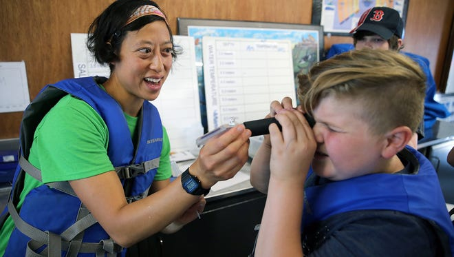 Sylvia Yang, SEA Discovery Center director, shows cybersecurity student Quentin Clark, 12, from Bainbridge Island how to view a saltwater sample. Western Washington University hosted a free cybersecurity camp for middle-schoolers at the SEA Discovery Center in Poulsbo.