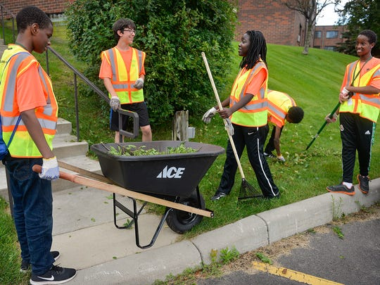 CareerONE summer camp participants talk as they finish picking up cuttings from shrubs at Benedict Village Thursday, July 21, in St. Cloud.The CareerONE program introduces kids to careers and teaches them the basics about applying for jobs and adopting a good work ethic.