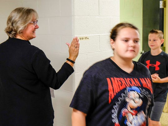 Michigamme Elementary School principal Heidi Bartle high-fives kids on the first day of school Sept. 5.