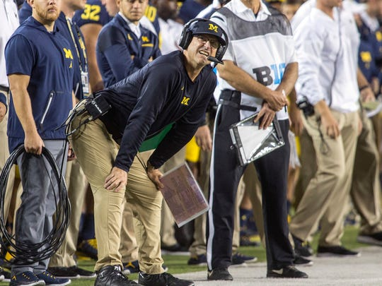 Michigan coach Jim Harbaugh looks at the scoreboard