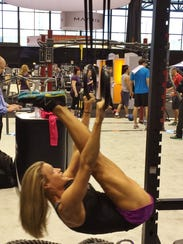Corrine Banks is shown on rings at a fitness convention