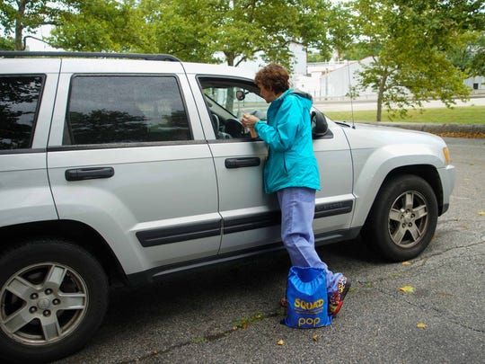 Dr. Sandra Gibney, an emergency medicine physician for St. Francis Hospital, teaches a woman in vehicle at a Wilmington park how to use naloxone to prevent an overdose death.
