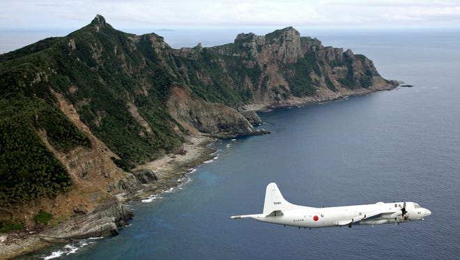 A Japanese surveillance plane flies over the Senkaku Islands in the East China Sea. China says the islands are in its air defense zone. Japan says China is trying to seize land that has been Japan's since the 19th century.