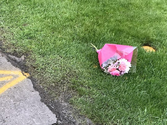 This bouquet of flowers lays near where Barbara Velasquez and her dog were struck and killed by a dump truck Monday on Suburban Drive in Big Flats.