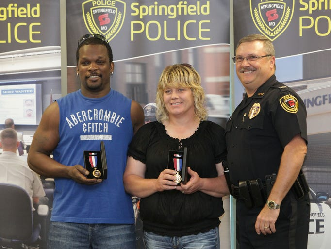 Carlos and Michelle Edwards pose with Police Chief Paul Williams Citizen Service Commendation medals during a ceremony at the Springfield Regional Police and Fire Training Center on Tuesday, July 1, 2014.