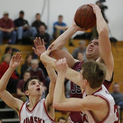 De Pere's Aaron Vopal goes strong to the basket against
