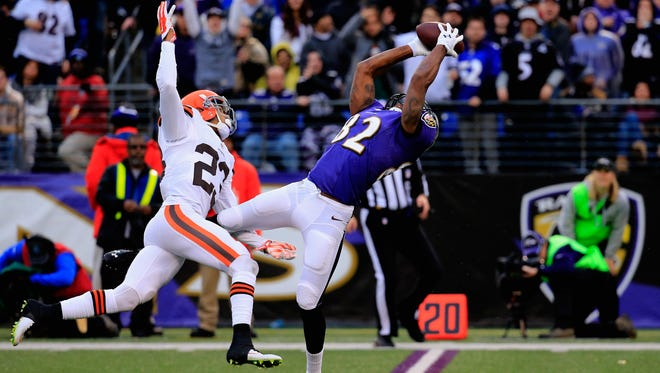 Wide receiver Torrey Smith #82 of the Baltimore Ravens makes a fourth quarter catch past the defense of cornerback Joe Haden #23 of the Cleveland Browns at M&T Bank Stadium on December 28, 2014 in Baltimore, Maryland.
