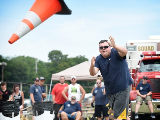 "First-place finisher and Hershey firefighter Colton Leonard tosses a cone during the 2016 Lebanon Area Fair Annual Fire Competition that took place on Sunday, July 24. The Cone Chucking contest is a single-person event that measures how close the cone thrower can get to a predetermined ""X"" on the ground."