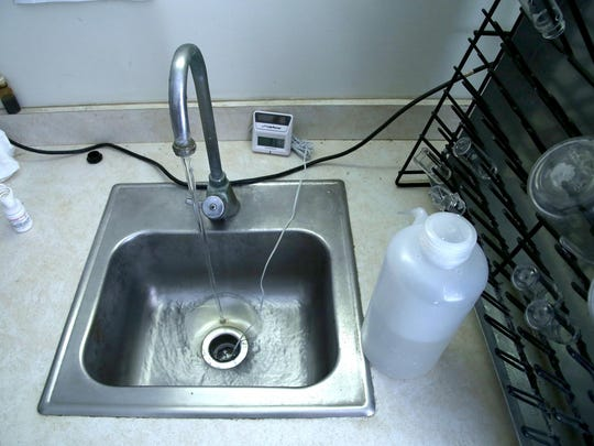 A water quality meter measures the purity of tap water